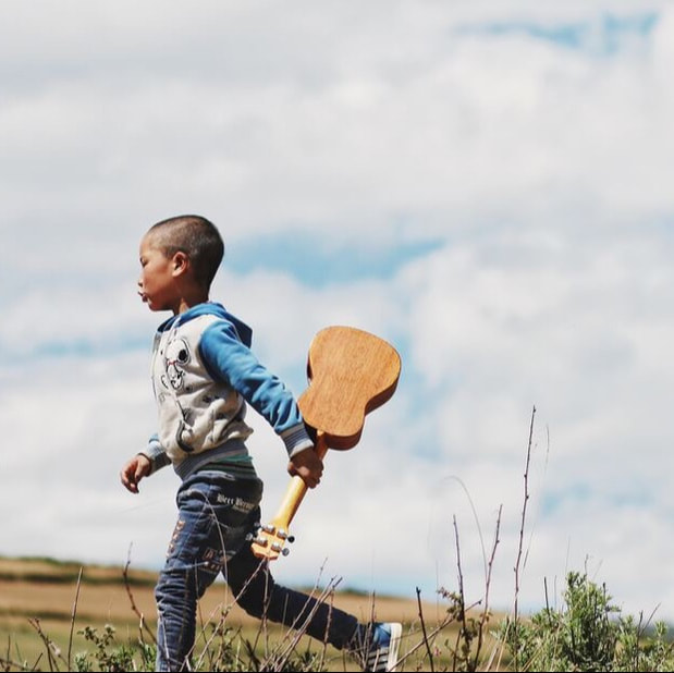 Child carrying ukulele.